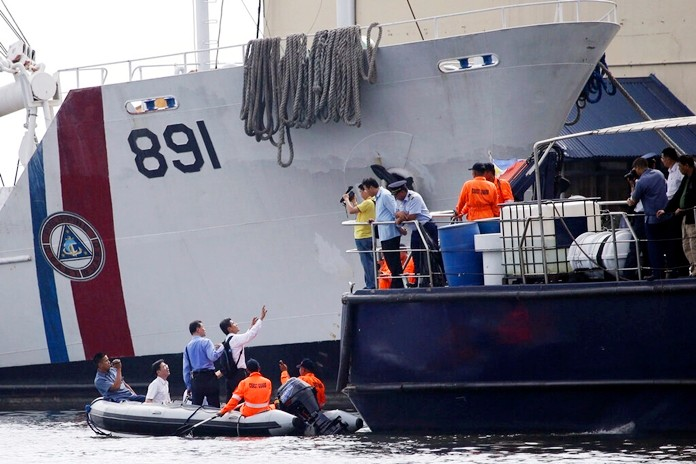 In this May 28, 2013, file photo, Taiwanese investigators inspect a Philippine ship involved in the alleged shooting of a Taiwanese fisherman. (AP Photo/Aaron Favila)