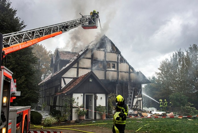 Firefighters extinguish a fire in a house in Muenster, Germany, Wednesday, Sept. 18, 2019. Two women and a police officer where injured by an explosion inside the house. (Bernd Thissen/dpa via AP)