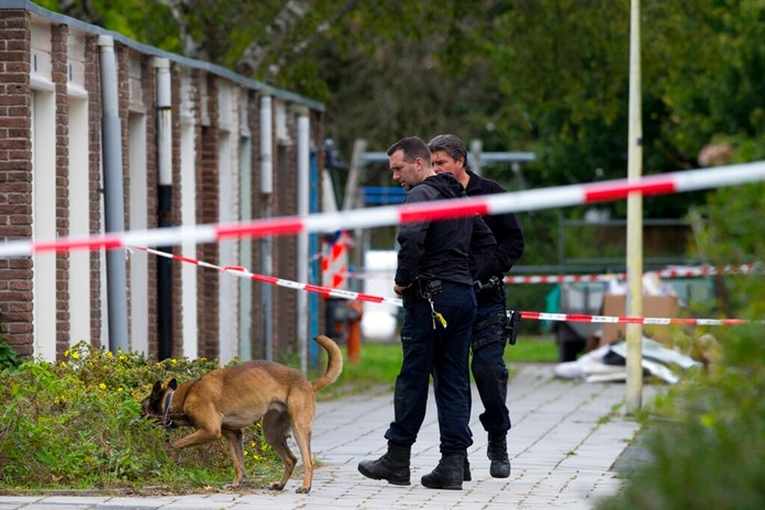 Forensic experts with a dog search for evidence in the area where a lawyer who represented a key witness in a major Dutch organized crime trial was gunned down in Amsterdam, Netherlands, Wednesday, Sept. 18, 2019. (AP Photo/Peter Dejong)