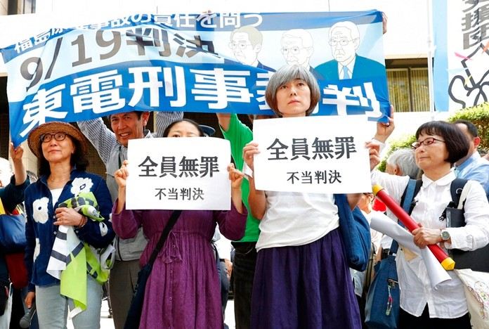 """A group of supporters of the trial shows banners reading """"unjust sentence"""" in front of Tokyo District Court in Tokyo Thursday, Sept. 19, 2019. (Satoru Yonemaru/Kyodo News via AP)"""