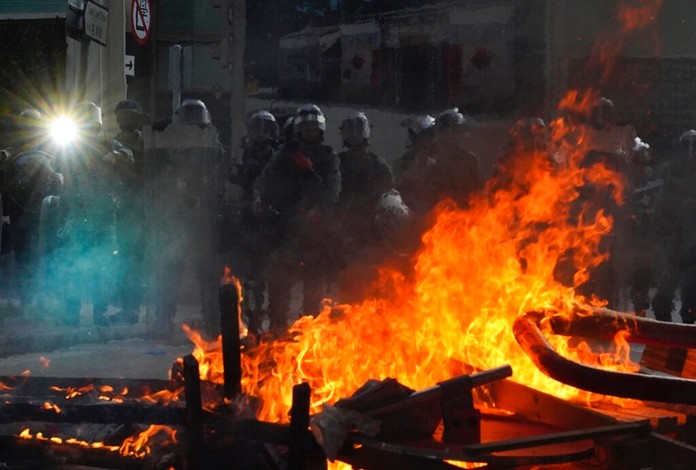 Police face a burning barricade during protests in Hong Kong on Saturday, Sept. 21, 2019. (AP Photo/Vincent Yu)
