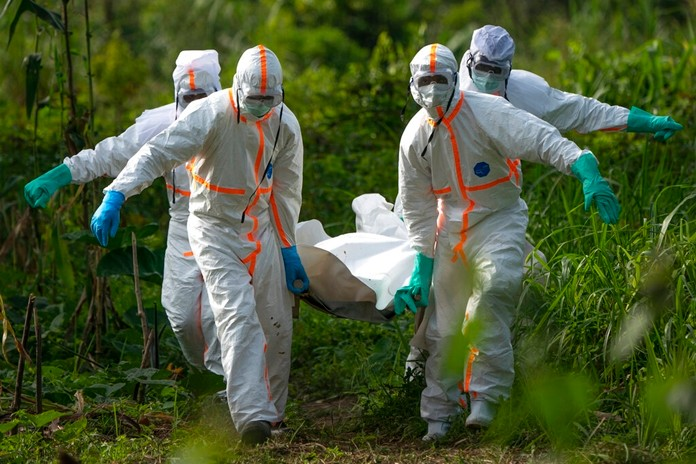 In this Sunday, July 14, 2019 photo, burial workers dressed in protective gear carry the remains of an Ebola victim in Beni, Congo. (AP Photo/Jerome Delay)