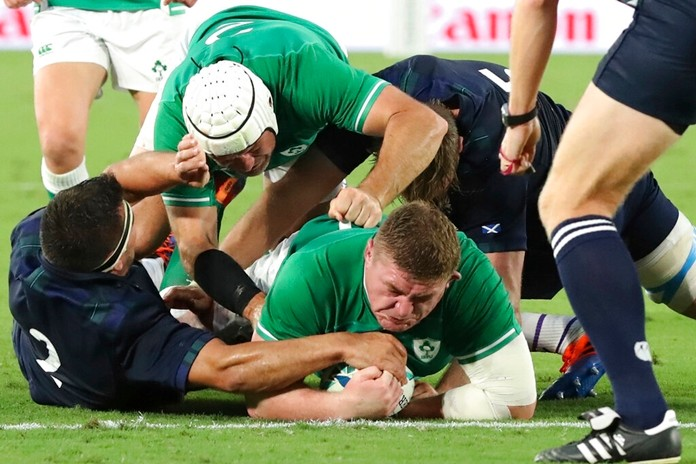 Ireland's Tadhg Furlong, center, carries the ball to score his team's third try during the Rugby World Cup Pool A game between Ireland and Scotland in Yokohama, Japan, Sunday, Sept. 22, 2019. (AP Photo/Eugene Hoshiko)