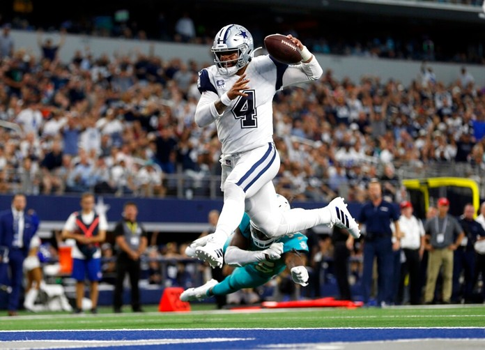 Dallas Cowboys quarterback Dak Prescott (4) gets past Miami Dolphins defensive back Walt Aikens (35) and into the end zone for a touchdown in the second half of an NFL football game in Arlington, Texas, Sunday, Sept. 22, 2019. (AP Photo/Ron Jenkins)