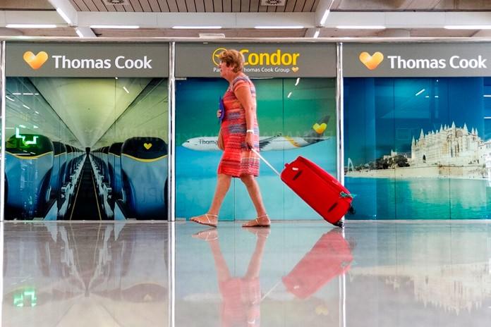 A passenger walks past a closed Thomas Cook office at Palma de Mallorca airport on Monday, Sept. 23, 2019. (AP Photo/Francisco Ubilla)