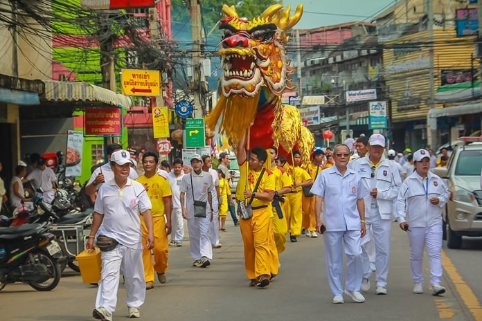 Sawang Boriboon Thammasathan Foundation President Wisit Chaowalitnittithum leads the dragon and lion parade through Naklua streets during last year's event.