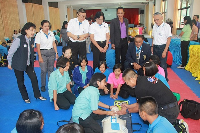 Rotarians and students watch intensely as Naval Captain Bunlue Buasomboon explains the proper method of CPR and use of the AED to one of the students.