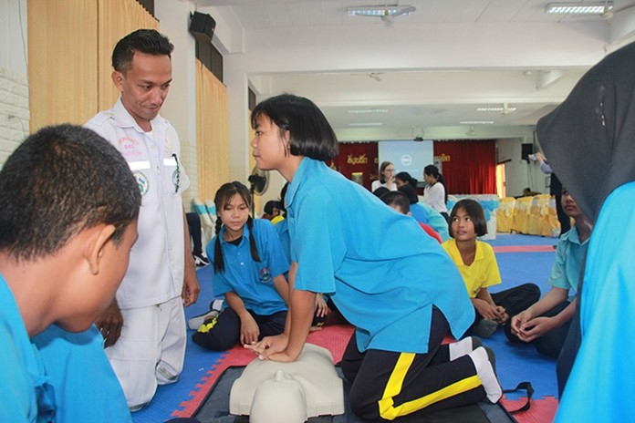 A student is in full concentration as she performs CPR on a training mannequin.