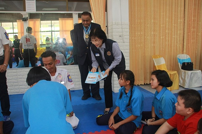 President Suphan Wiboonma distributes training manuals to the participants.