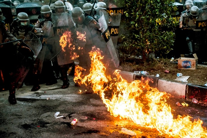 Riot police officers react as a molotov cocktail explodes nearby during a clash with student protesters in Bandung, West Java, Indonesia, Monday, Sept. 30, 2019. (AP Photo/Kusumadireza)
