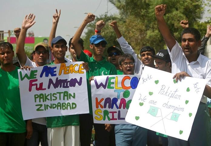 Pakistani cricket fans celebrate the Pakistan--Sri Lanka cricket series outside the National stadium in Karachi, Pakistan, Monday, Sept. 30, 2019. (AP Photo/Fareed Khan)