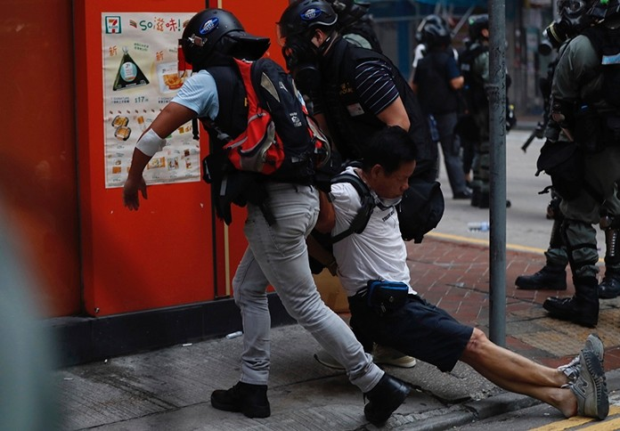 An injured anti-government protester is attended to by others during a clash with police in Hong Kong, Tuesday, Oct. 1, 2019. (AP Photo/Gemunu Amarasinghe)