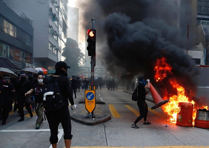 Anti-government protesters set fire to block traffic in Hong Kong, Tuesday, Oct. 1, 2019. (AP Photo/Gemunu Amarasinghe)