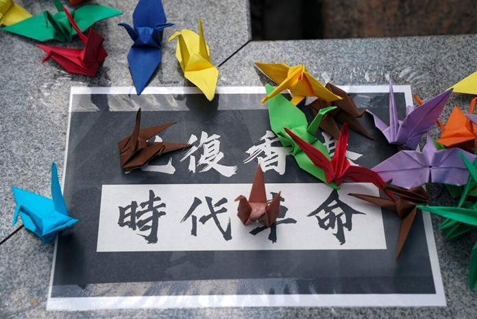 """Students fold paper origami cranes on a poster that reads, """"Liberate Hong Kong. Revolution of our times,"""" as they march to the Chinese University to show support to those students who were arrested by police in Hong Kong, Thursday, Oct. 3, 2019. (AP Photo/Vincent Thian)"""