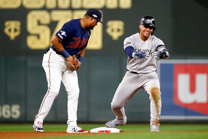 New York Yankees' Gleyber Torres, right, celebrates in front of Minnesota Twins second baseman Luis Arraez, left, after hitting a double in the seventh inning. (AP Photo/Bruce Kluckhohn)