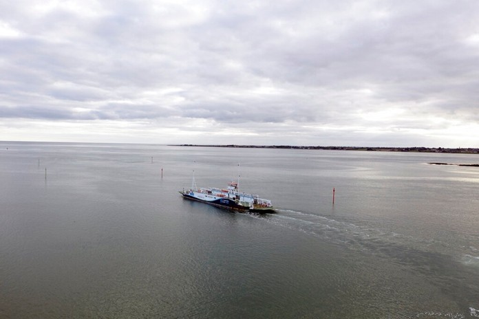 A small ferry sails across the calm waters of Carlingford Lough connecting Northern Ireland with the Republic of Ireland, Wednesday, Oct. 2, 2019. (AP Photo/David Keyton)