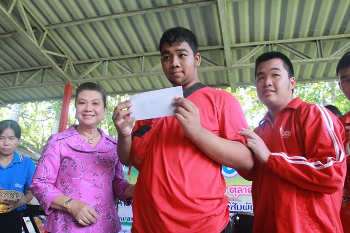 Jamnien Chaiyanit presents a scholarship to a very happy boy.