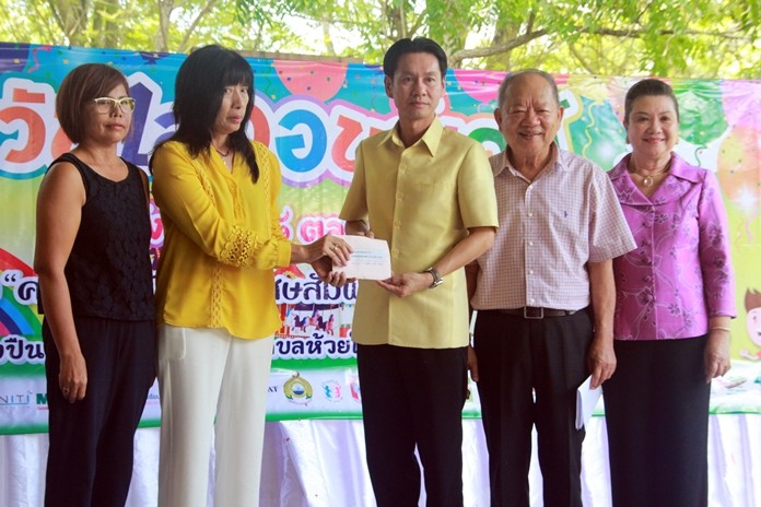 Representatives of the local community make a donation for children's scholarships.