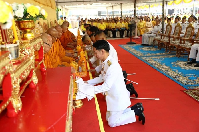 Banglamung District Chief Amnart Charoensri leads officials in presenting alms to monks for Auk Pansaa.