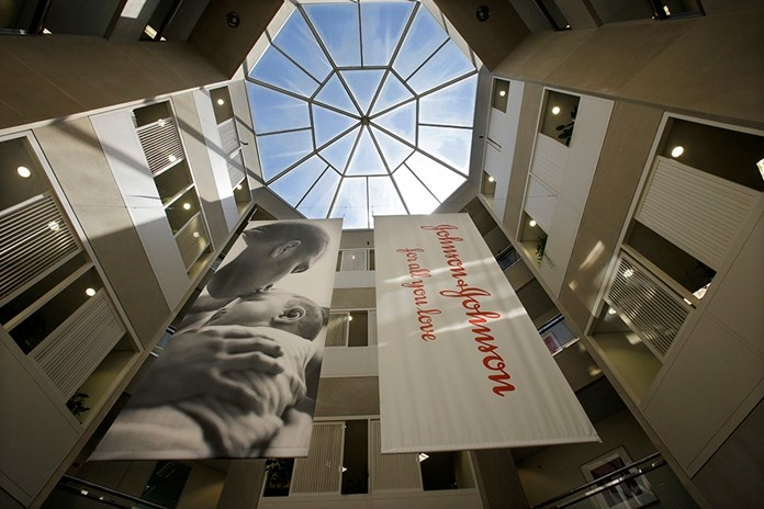 In this July 30, 2013, file photo, large banners hang in an atrium at the headquarters of Johnson & Johnson in New Brunswick, N.J. Johnson & Johnson has agreed to a $117 million multistate settlement over allegations it deceptively marketed its pelvic mesh products, which support women's sagging pelvic organs. (AP Photo/Mel Evans, File)