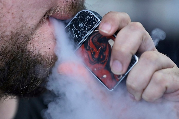 In this Friday, Oct. 4, 2019 photo, a man using an electronic cigarette exhales in Mayfield Heights, Ohio. Vaping-related illnesses in the U.S. are still rising, though at a slightly slower pace. (AP Photo/Tony Dejak)