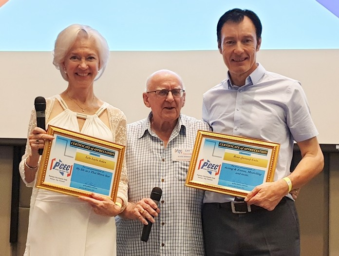MC Les Edmonds presents the PCEC's Certificate of Appreciation to Lela Aukes and Ross Cain for their enlightening and entertaining presentation about acting and modelling for westerners in Thailand.