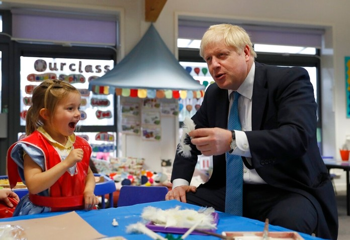 Britain's Prime Minister Boris Johnson gestures as he participates in an art class with Scarlet Fickling aged 4, in at St Mary's and All Saints Primary School in Beaconsfield, England, Friday, Oct. 11, 2019. (AP Photo/Alastair Grant, Pool)