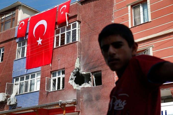 A child stands across from a building damaged by a mortar fired from inside Syria, in Akcakale, Sanliurfa province, southeastern Turkey, Sunday, Oct. 13, 2019. Incoming shells fired from northeastern Syria hit the house earlier on Sunday. (AP Photo/Lefteris Pitarakis)