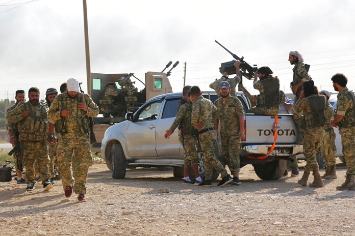 In this Saturday, Oct. 12, 2019 photo, Turkey-backed Syrian fighters enter Ras al-Yan, Syria. Turkey's military says it has captured a key Syrian border town Ras al-Ayn under heavy bombardment in its most significant gain as its offensive against Kurdish fighters presses into its fourth day. (AP Photo)