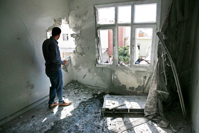 A person inspects the damage on a building hit by a mortar fired from inside Syria, in Akcakale, Sanliurfa province, southeastern Turkey, Sunday, Oct. 13, 2019. Two residents were at the house and were evacuated. (AP Photo/Lefteris Pitarakis)