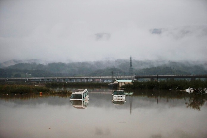 Two vehicles are submerged in floodwaters Monday, Oct. 14, 2019, in Hoyasu, Japan. (AP Photo/Jae C. Hong)