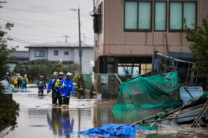 Search and rescue team members wade through floodwaters Monday, Oct. 14, 2019, in Hoyasu, Japan. (AP Photo/Jae C. Hong)