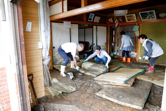 Residents clean a house damaged by Typhoon Hagibis, in Marumori town, Miyagi prefecture, Japan Monday, Oct. 14, 2019. (Kyodo News via AP)