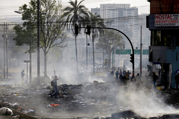 Pedestrians walk among the debris of barricades set by anti-government protesters in Quito, Ecuador, Sunday, Oct. 13, 2019. President Lenin Moreno ordered the army onto the streets of Ecuador's capital Saturday after a week and a half of protests over fuel prices devolved into violent incidents. (AP Photo/Fernando Vergara)