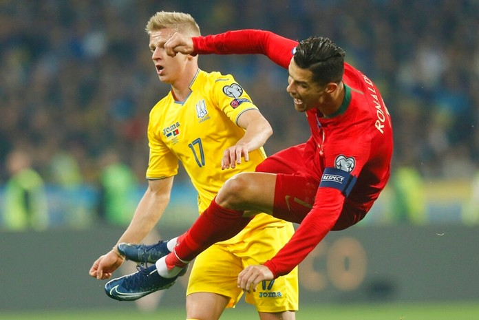 Portugal's Cristiano Ronaldo, right, fights for the ball with Ukraine's Oleksandr Zinchenko during the Euro 2020 group B qualifying soccer match between Ukraine and Portugal at the Olympiyskiy stadium in Kyiv, Ukraine, Monday, Oct. 14, 2019. (AP Photo/Efrem Lukatsky)
