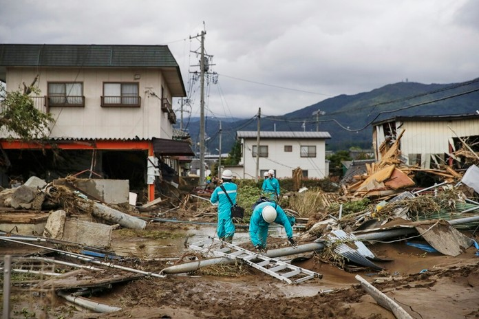 Utility workers survey damages in a neighborhood devastated by Typhoon Hagibis Tuesday, Oct. 15, 2019, in Nagano, Japan. (AP Photo/Jae C. Hong)