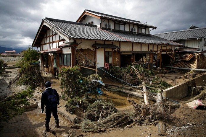 A man surveys a home damaged by Typhoon Hagibis Tuesday in Nagano. More victims and more damage have been found in typhoon-hit areas of central and northern Japan, where rescue crews are searching for people still missing. (AP Photo/Jae C. Hong)