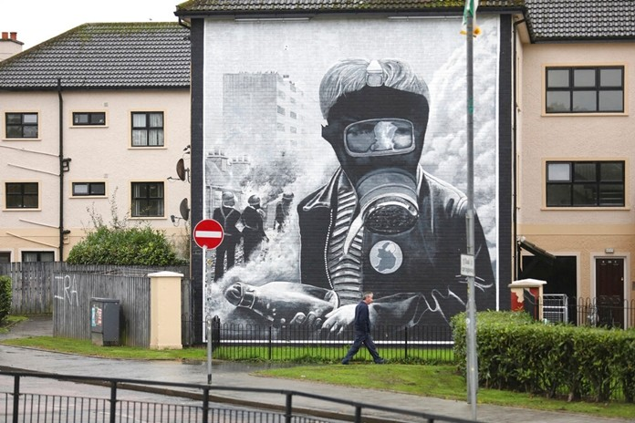 In this photo dated Monday Oct. 14, 2019 a man walks past an Irish Republican mural depicting scenes of the Battle of the Bogside area of Derry in August 1969. (AP Photo/Peter Morrison)
