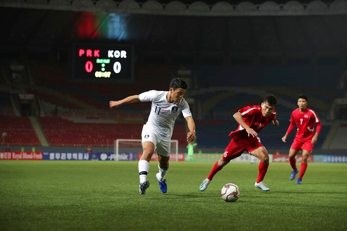 In this photo provided by the Korea Football Association, South Korea's Hwang Hee-chan, left, fights for the ball against North Korea's Kim Chol Bom during their Asian zone Group H qualifying soccer match for the 2022 World Cup at an empty Kim Il Sung Stadium in Pyongyang, North Korea, Tuesday, Oct. 15, 2019. (The Korea Football Association via AP)