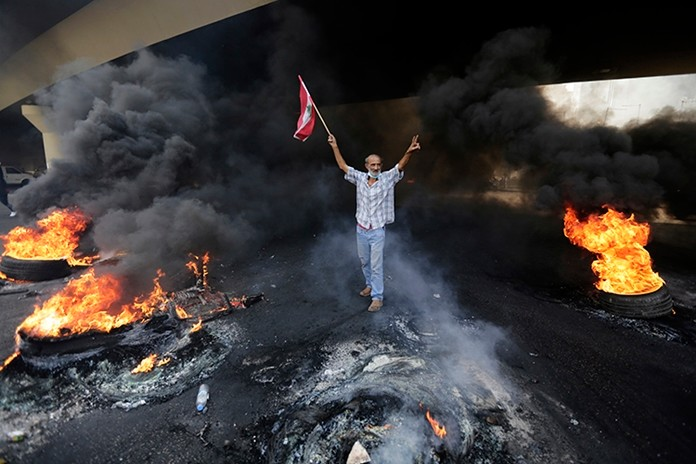 Anti-government protesters set fire to tires to block a road during a protest in Beirut, Lebanon, Friday, Oct. 18. (AP Photo/Hassan Ammar)