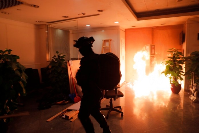 A protester sets fire to a Bank of China branch in Hong Kong, Sunday, Oct. 20, 2019. Hong Kong protesters again flooded streets on Sunday, ignoring a police ban on the rally and demanding the government meet their demands for accountability and political rights. (AP Photo/Kin Cheung)