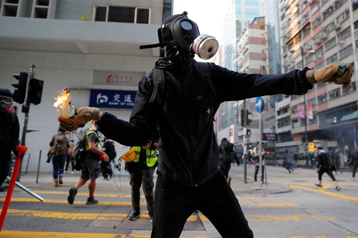 A protester prepares to throw a Molotov cocktail at a police station in Hong Kong, Sunday, Oct. 20, 2019. (AP Photo/Kin Cheung)