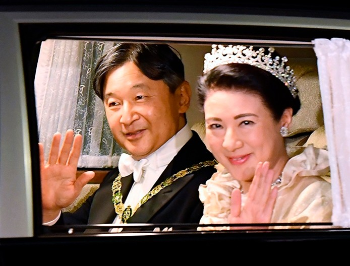 Japan's Emperor Naruhito, left, and Empress Masako, right, wave, as they depart for the Imperial Palace for the court banquet, in Tokyo, Tuesday, Oct. 22, 2019. Japan's Naruhito proclaimed himself Emperor during an enthronement ceremony at the Imperial Palace, declaring himself the country's 126th monarch. (Ren Onuma/Kyodo News via AP)