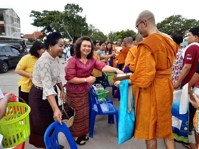 Buddhists present alms to monks at Wat Boonsamphan.