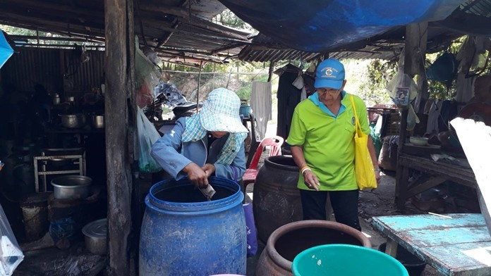 Arunothai Community Assistant Head Amnuay Muangthong and volunteers dumped water sources, flipped over buckets and containers, and dropped abate into puddles and other standing water to kill mosquitos in their battle to prevent dengue fever.