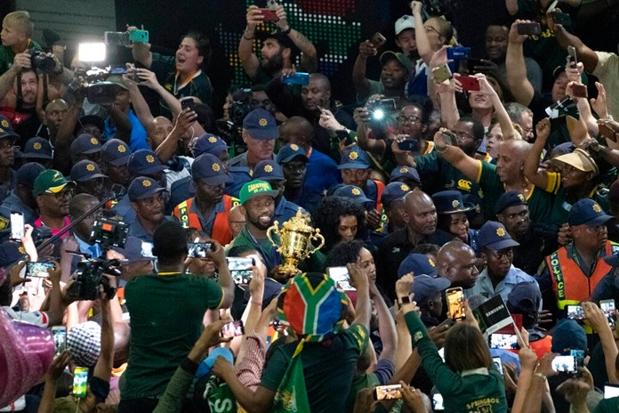 South African Rugby team captain Siya Kolisi holds the Webb Ellis Cup as he is greeted by hundreds of fans upon his arrival at Johannesburg's O.R. Tambo airport Tuesday Nov. 5, 2019. (AP Photo/Jerome Delay)