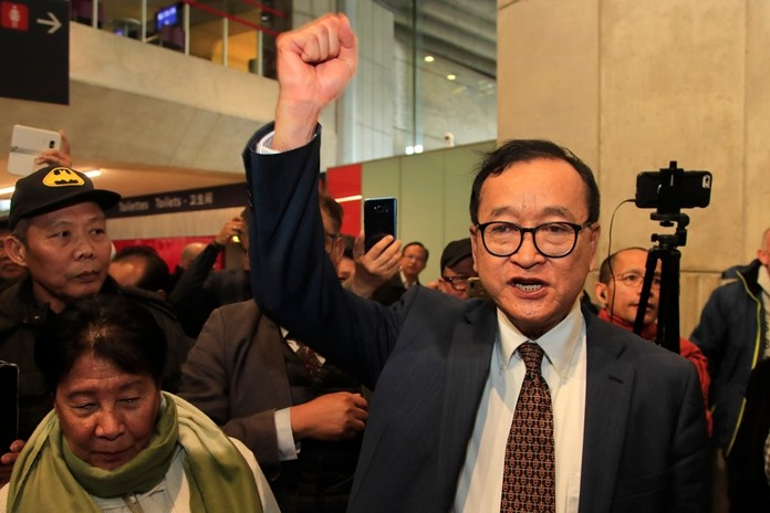 Cambodia's most prominent opposition politician Sam Rainsy clenches his fist as he is attempting to return to Cambodia Thursday, Nov. 7, 2019 at Charles de Gaulle airport, north of Paris. (AP Photo/Michel Euler)