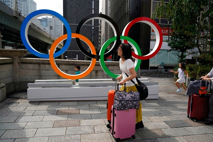 In this Aug. 19, 2019, file photo, tourists walk with their luggage past the Olympic rings in Tokyo. Frustrated residents of Japan got another shot at attending next year's Tokyo Olympics when organizers on Friday, Nov. 8, 2019, put about 1 million more tickets into the latest lottery. (AP Photo/Jae C. Hong, File)