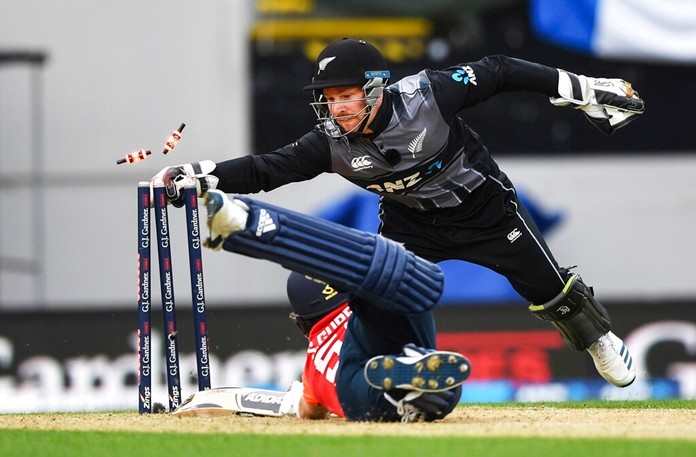 New Zealand wicket keeper Tim Seifert whips the bails off as he runs out England batsman Sam Curran during their T20 cricket match at Eden Park, Auckland, New Zealand, Sunday, Nov. 10, 2019. (Andrew Cornaga/Photosport via AP)