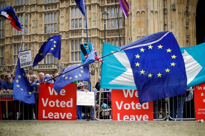 In this Sept. 3, 2019, file photo, leave and remain supporters try to block each others' banners as they protest opposite Parliament Square in London. Internet companies say they're working to fight misinformation ahead of next month's general election in the United Kingdom, but bogus online claims and misleading political ads remain a threat due to government inaction. (AP Photo/Matt Dunham, File)